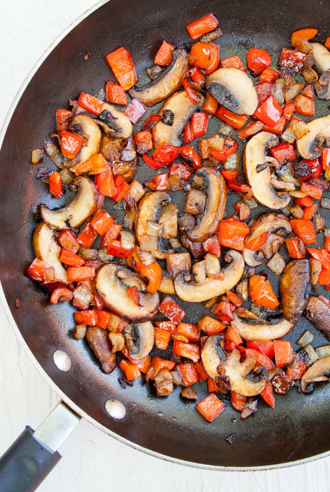 Mushrooms and red pepper in a pan.