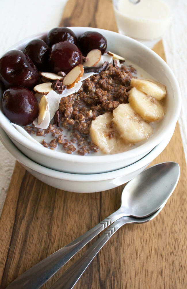 Chocolate Quinoa Breakfast Bowl with almond milk in the background.