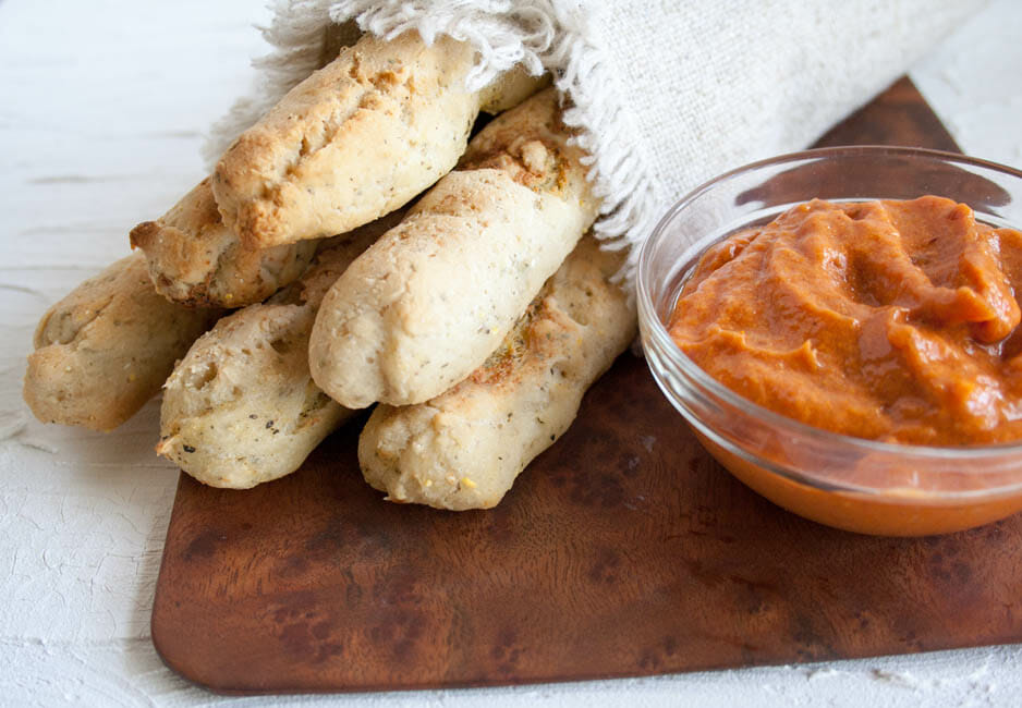 Tofu Ricotta Stuffed Breadsticks close up with dipping sauce.