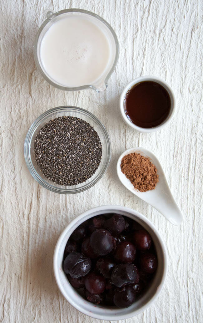 Pitcher of almond milk, bowl of chia seeds, spoonful of cacao powder, ramekin of maple syrup, and bowl of cherries.