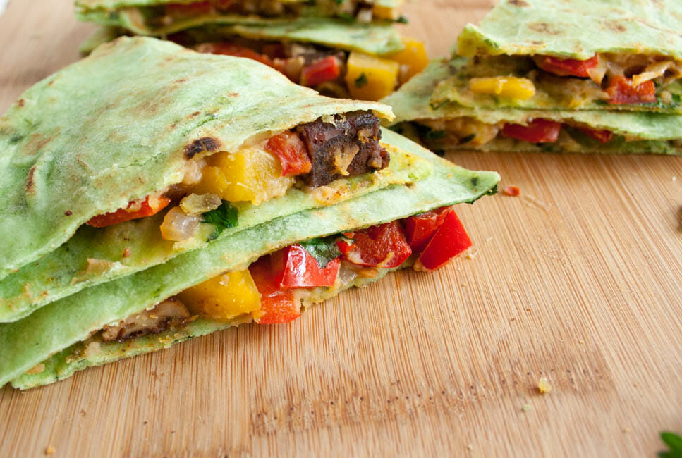 Tofu Quesadilla loaded with mango, red pepper, and chipotle hummus. close up.