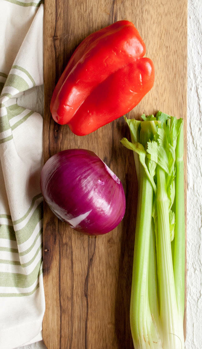 Celery, red pepper, and red onion on a cutting board.