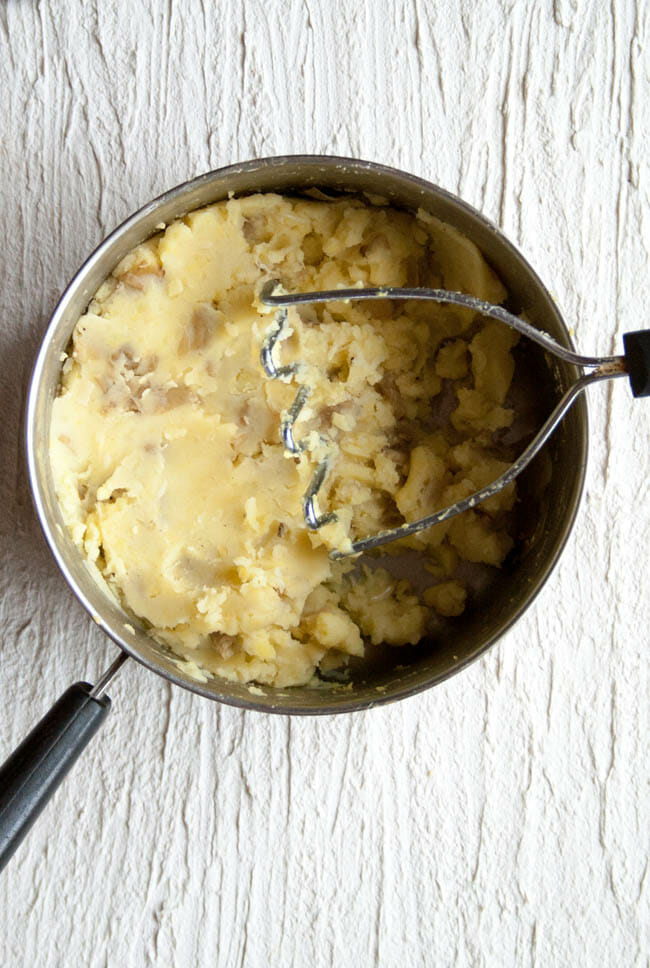 Vegan Mashed Potatoes with Roasted Garlic in pot with potato masher.