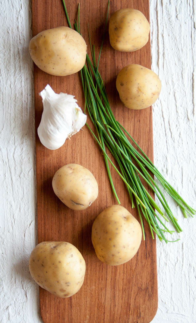Ingredients for Vegan Mashed Potatoes with Roasted Garlic on cutting board: yukon gold potatoes, chives, ad garlic.