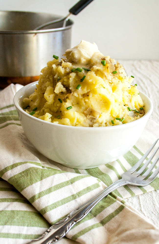 Vegan Mashed Potatoes with Roasted Garlic with pot in the background.
