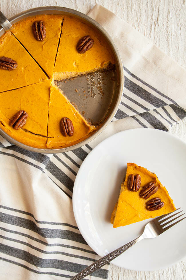 Creamy Vegan Pumpkin Cheesecake birds eye view in baking pan and a slice on a plate.