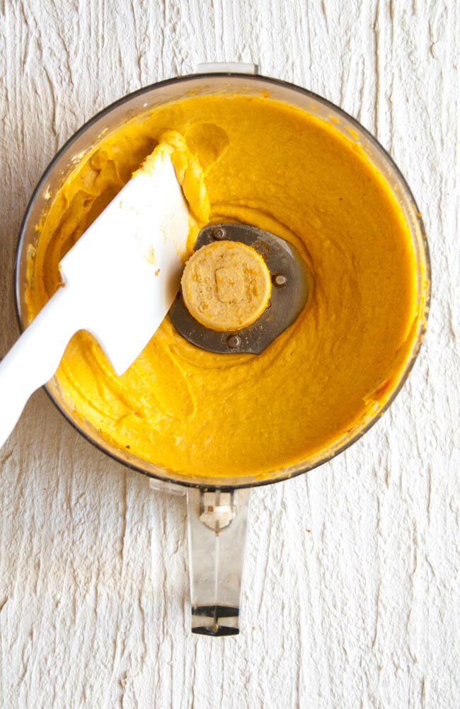 Creamy Vegan Pumpkin Cheesecake filling in food processor with spatula.
