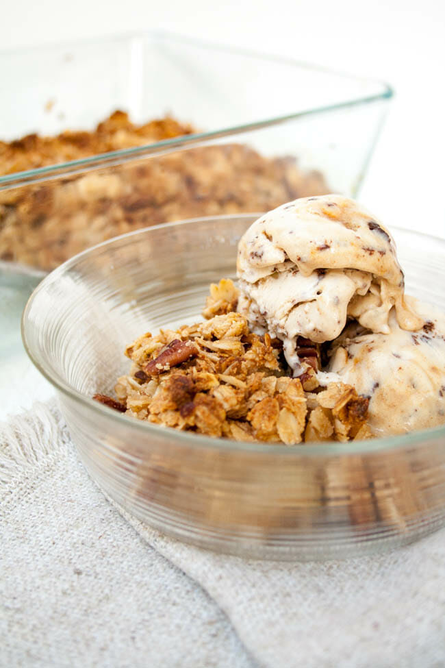 Vegan Apple Crisp in a bowl with vegan ice cream.
