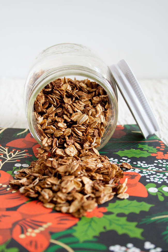 Gingerbread Granola spilling out of a mason jar.
