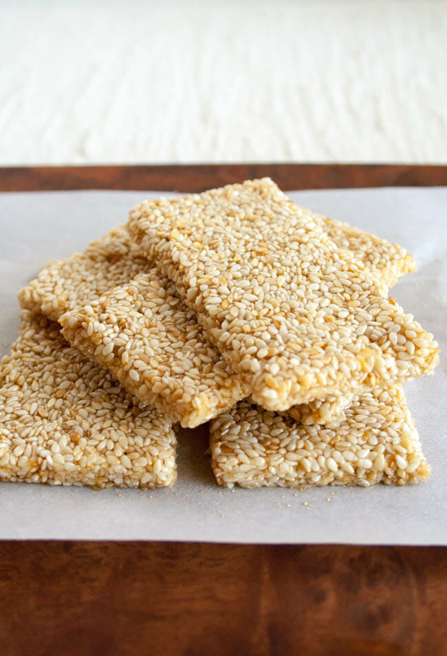 Sesame Crunch Bars stacked on parchment paper.
