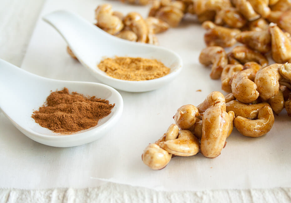 Sweet and Spicy Cashews next to spices in spoons