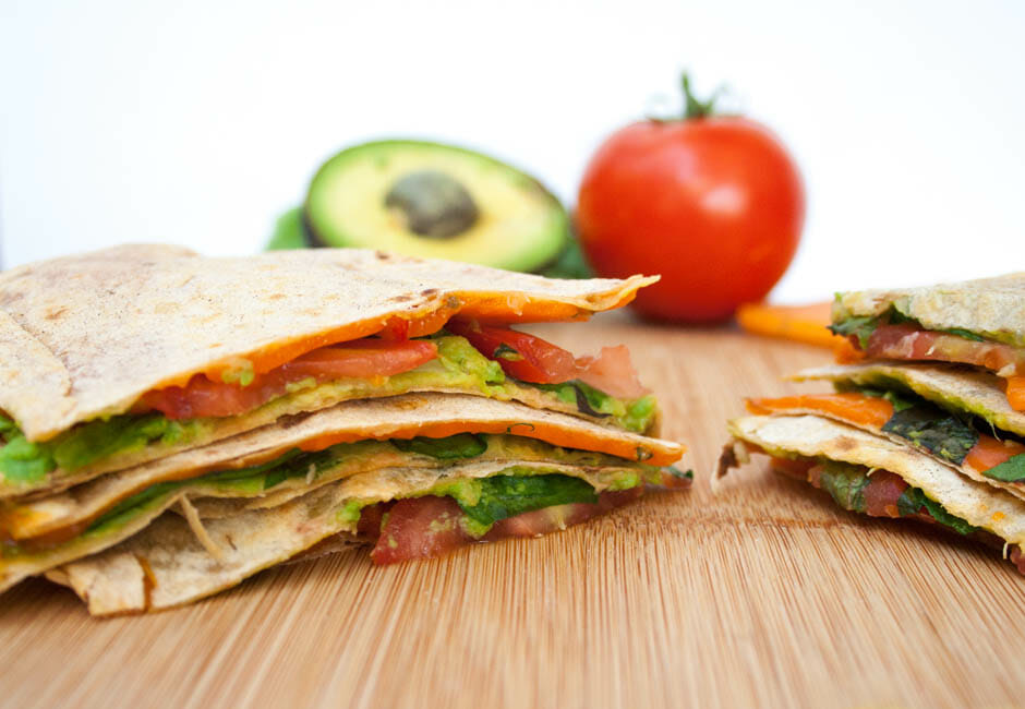 Avocado Quesadilla with lettuce, tomato, and vegan cheese on cutting board.