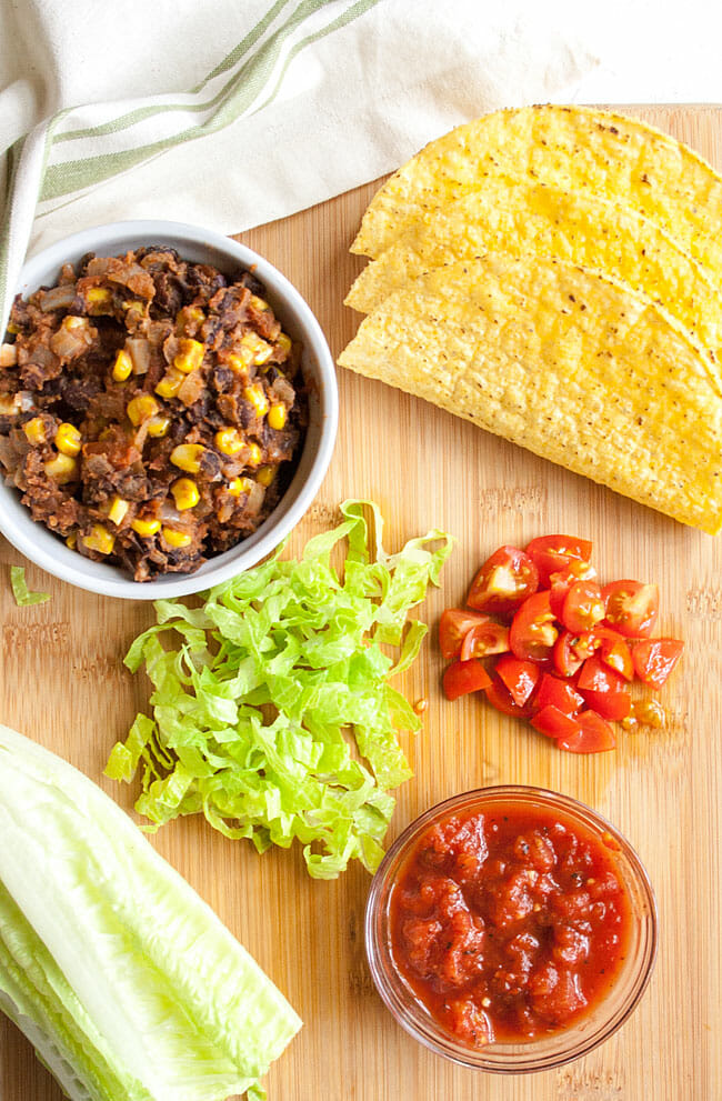 Vegan taco ingredients on a cutting board: black bean and corn mixture, chopped lettuce, tomatoes, salsa, and hard shell tacos.
