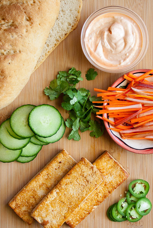 Vegan Bánh Mì ingredients on cutting board bird's eye view.