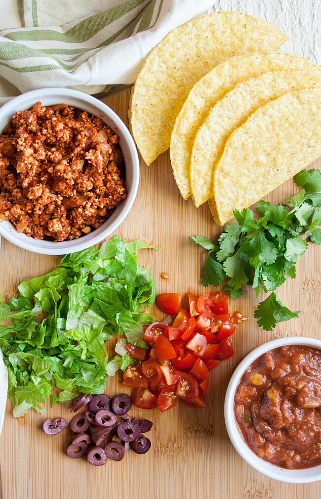 Spicy Vegan Taco ingredients on a cutting board: taco shells, crumbled tofu, salsa, cilantro, chopped lettuce, Kalamata olives, and chopped cherry tomatoes.