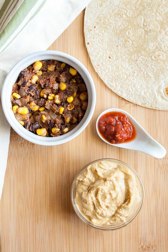 Salsa, black bean and corn mixture, chipotle hummus, and tortilla on a cutting board.