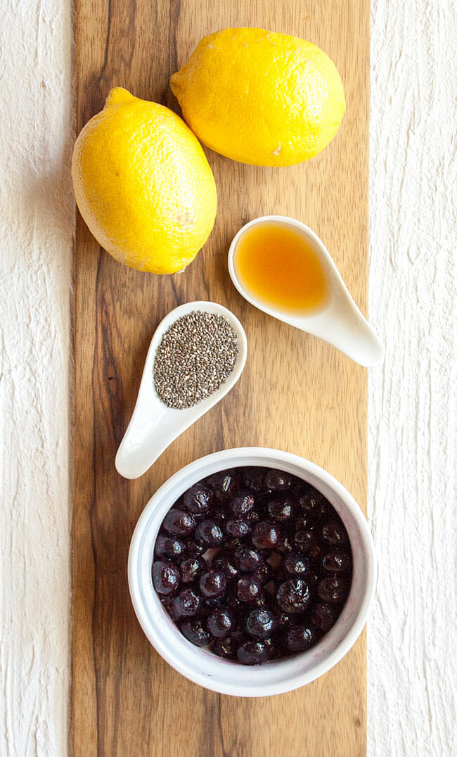 Bowl of blueberries, two lemons, and spoonfuls of maple syrup and chia seeds on a cutting board.