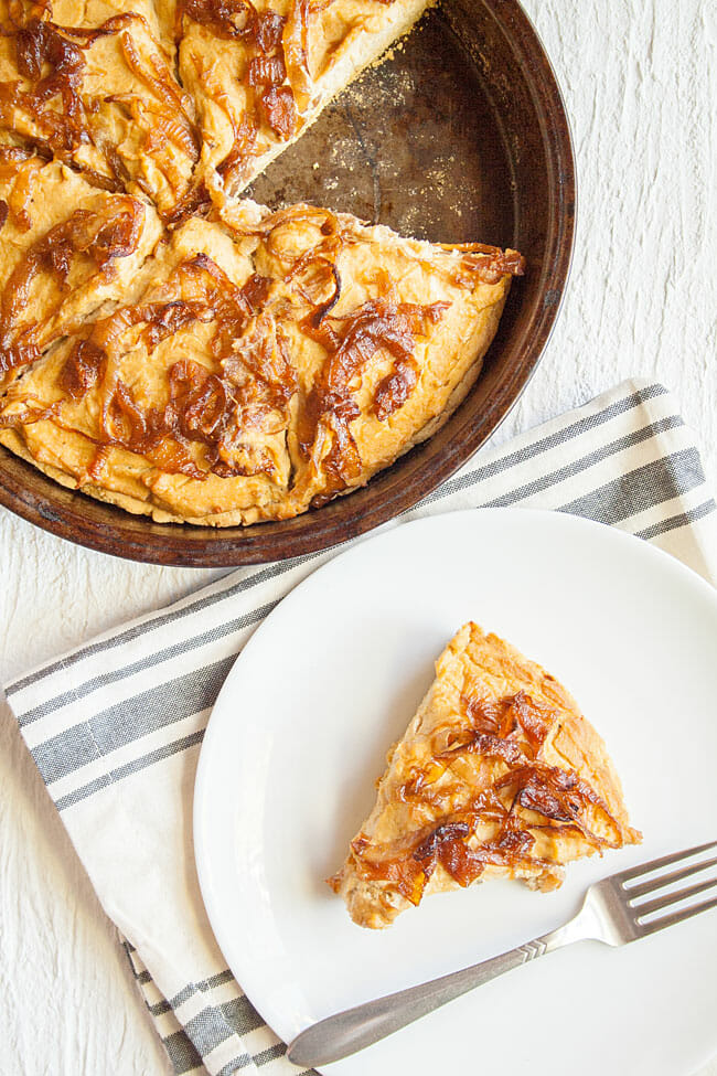Caramelized Onion Quiche on a plate with pan of quiche next to it.