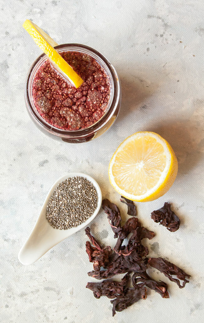Chia Fresca birds eye view with lemon, chia seeds, and hibiscus flowers.