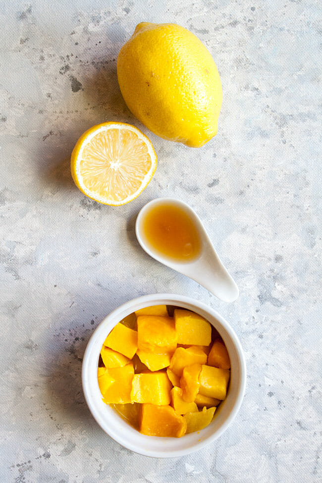 Bowl of chopped mango, lemons, and spoonful of maple syrup birds eye view.