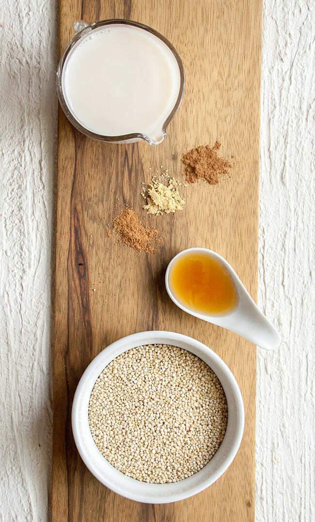Pitcher of almond milk, spoonful of maple syrup, bowl of dry quinoa, and spices on a cutting board.