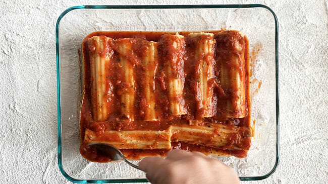 Manicotti pasta recipe in baking dish with marinara sauce on top.