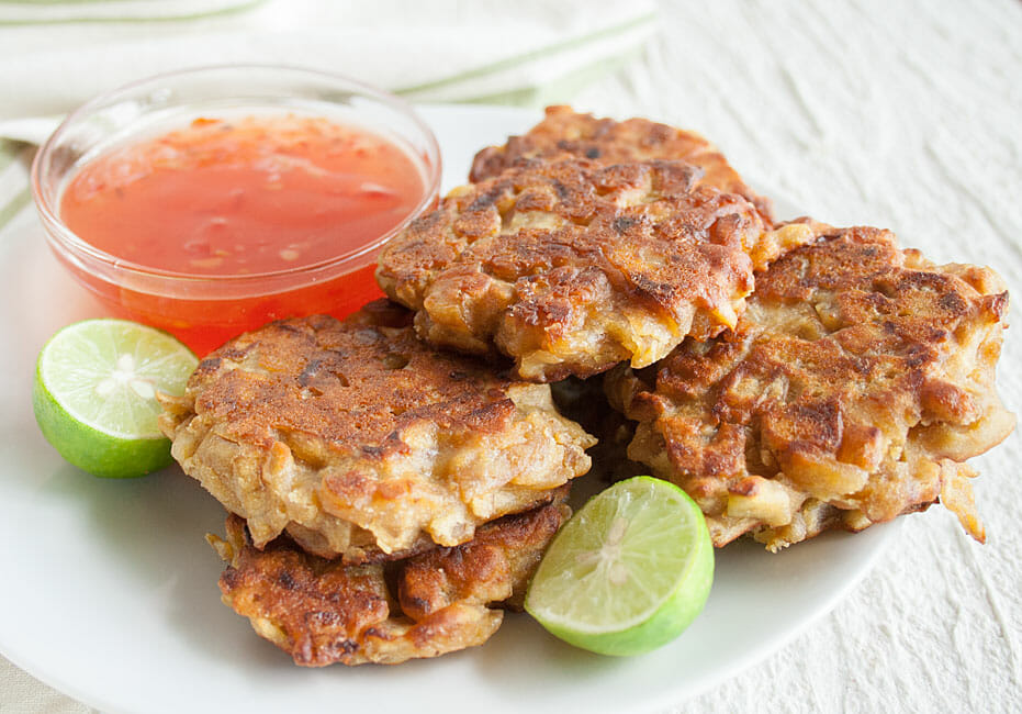 Onion Fritters on a plate with limes and sweet chili sauce.