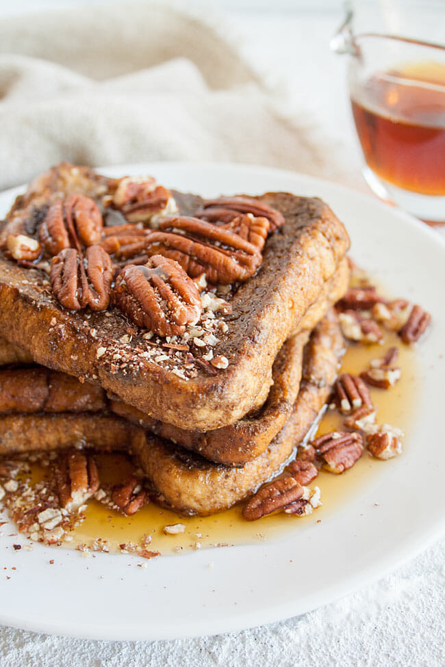 Gingerbread French Toast on a plate with pecans on top.