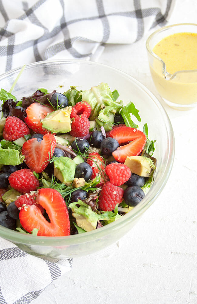 Avocado and Berry Salad with Turmeric Tahini Dressing in a bowl.