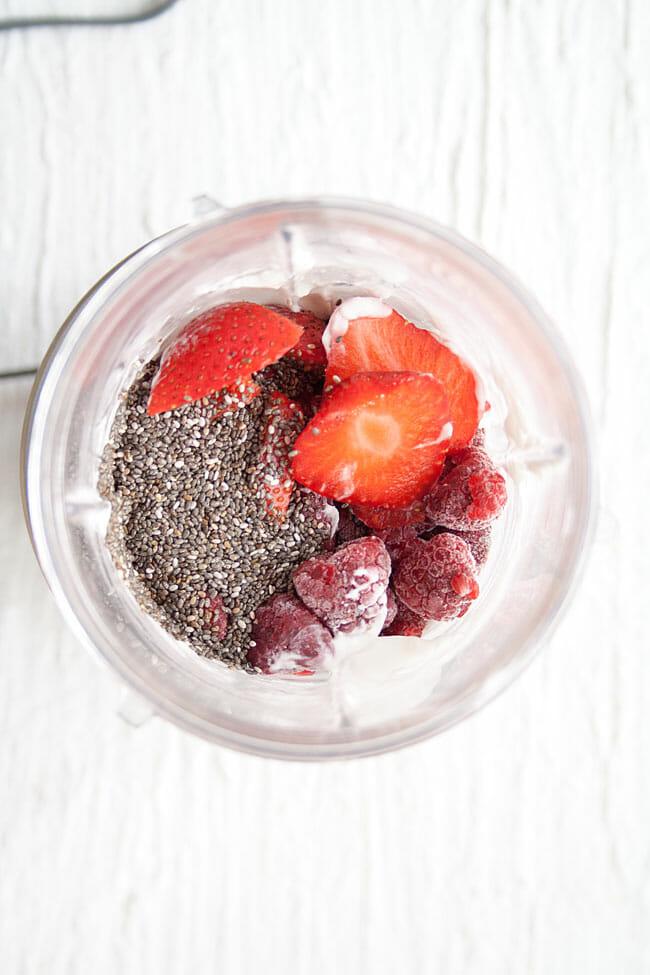 Strawberries, raspberries, coconut milk, and chia seeds in a Nutribullet.