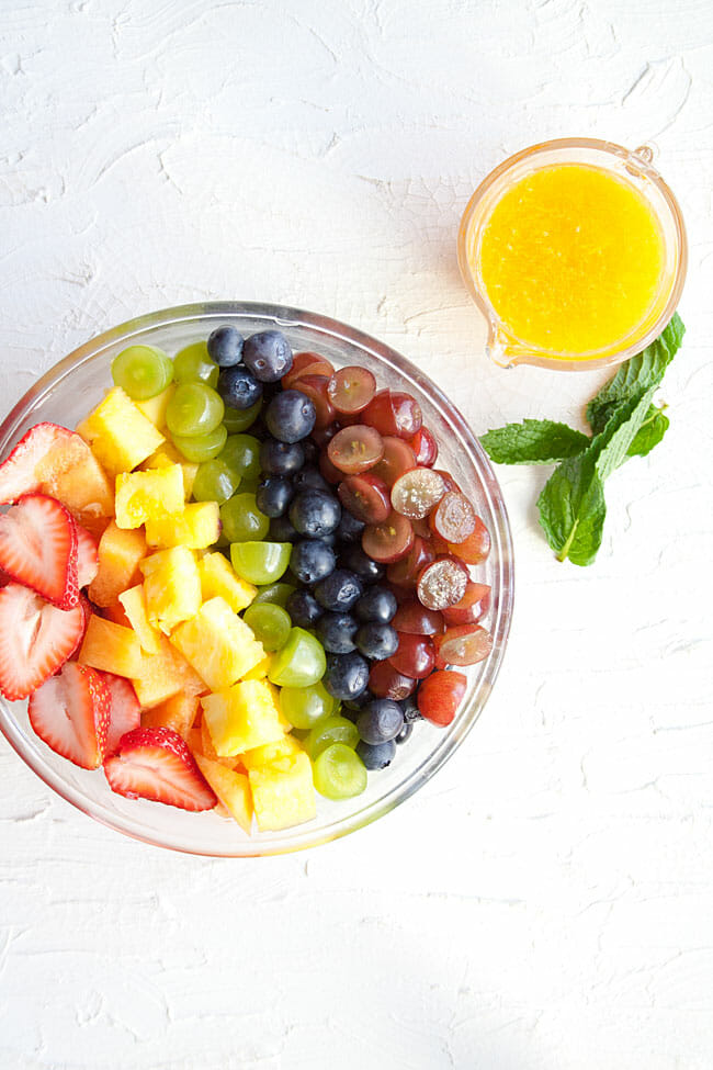 Rainbow Fruit Salad with citrus dressing and mint next to it bird's eye view.