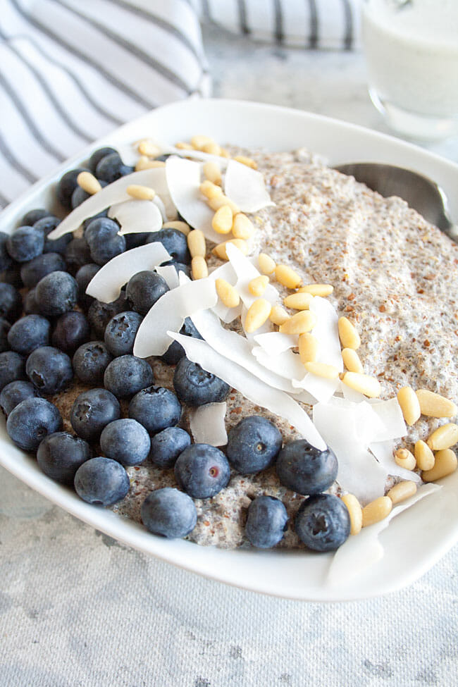 Spiced Chia Seed Porridge in bowl with blueberries, pine nuts, and coconut chips.