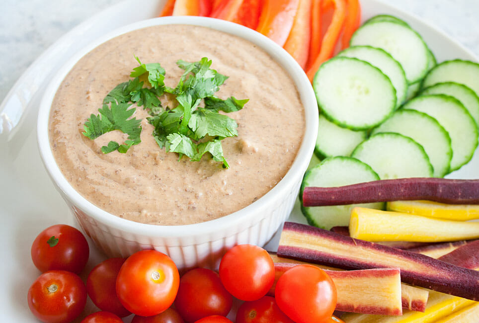 Spicy Black Bean Hummus on a plate with veggies.