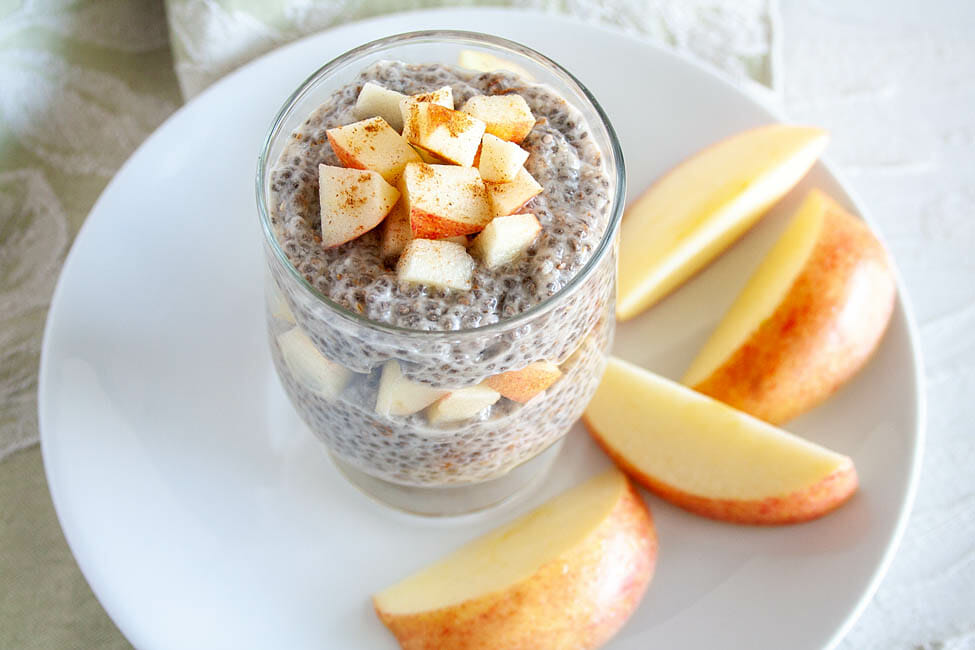 Chia Pudding in a jar with layers of chopped apple. Apple slices on a plate in the background.