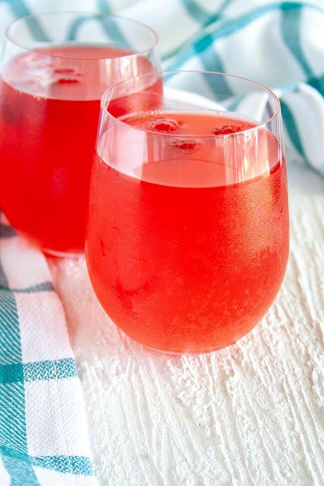 Raspberry Kombucha in two wine glasses.