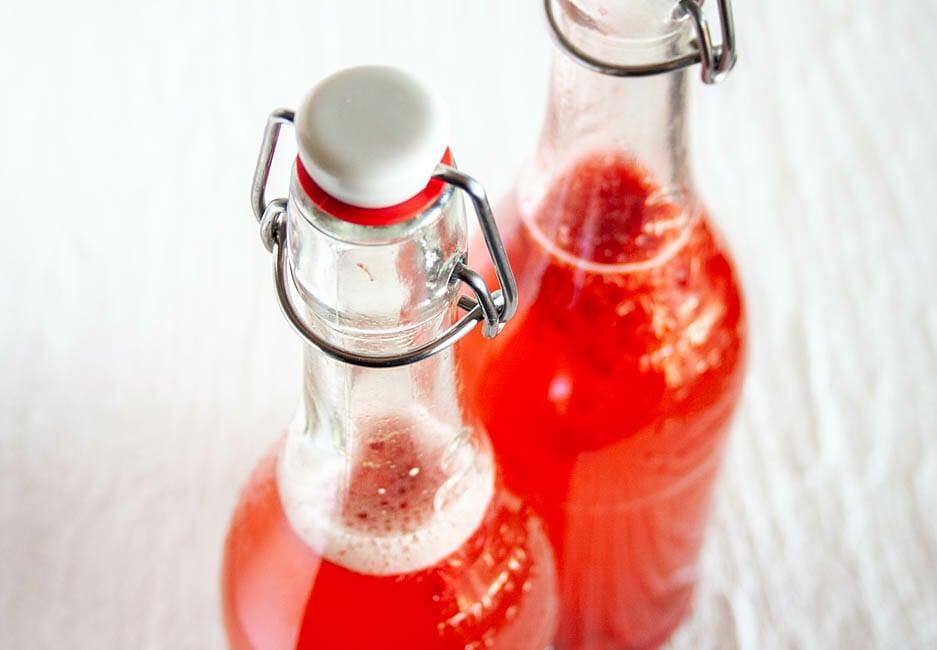 Raspberry Kombucha in two pop top bottles close up.