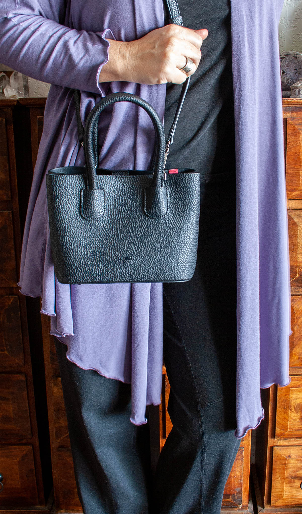 Photo of me in black pants, black t-shirt, lavender cover up and black Cher Micro handbag on my shoulder.