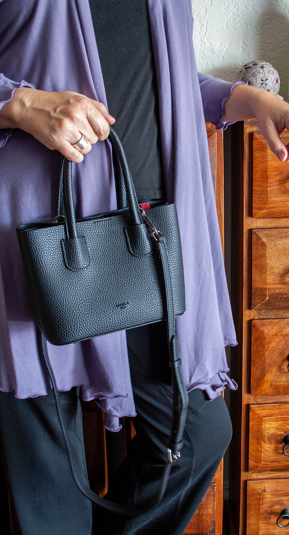 Photo of me in black pants, black t-shirt, lavender cover up and black Cher Micro handbag in my hand.