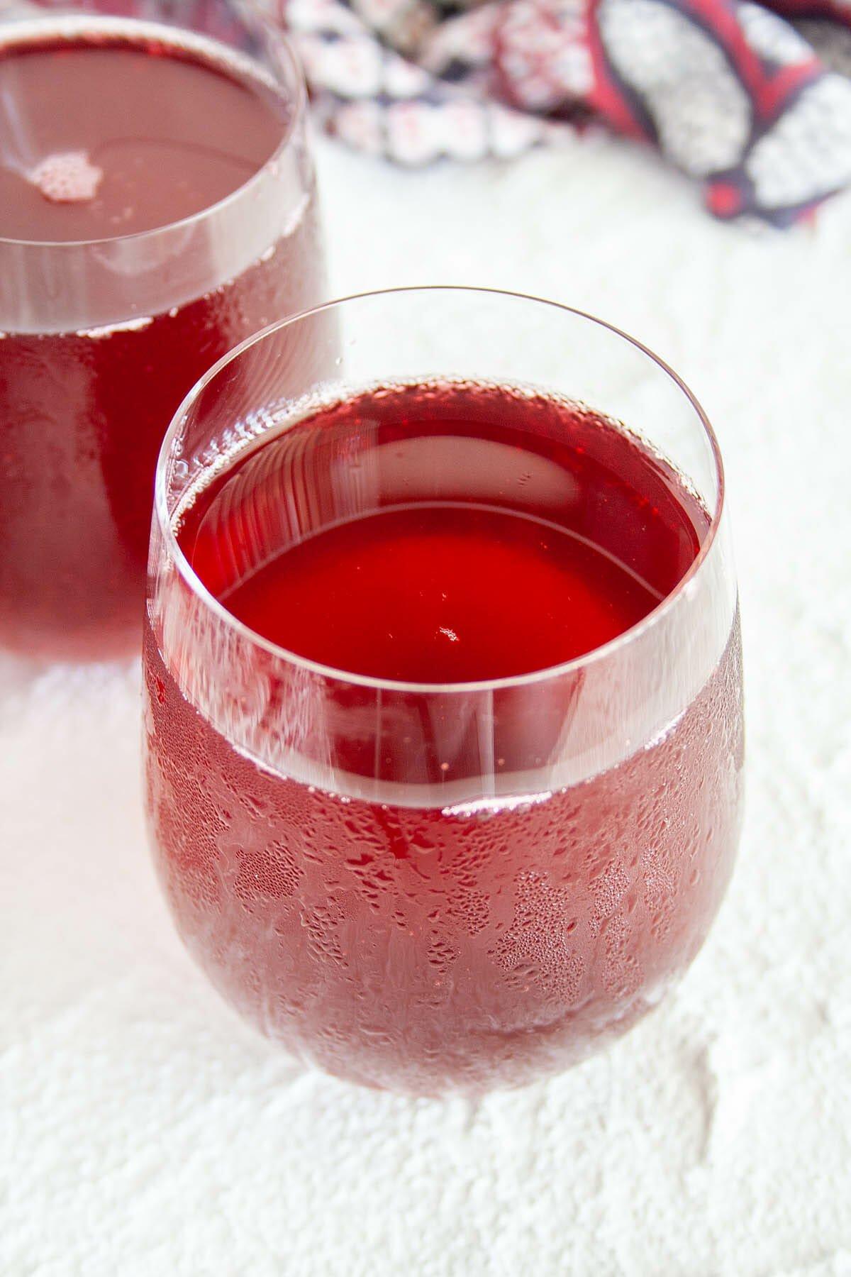 Cherry Kombucha in two wine glasses.