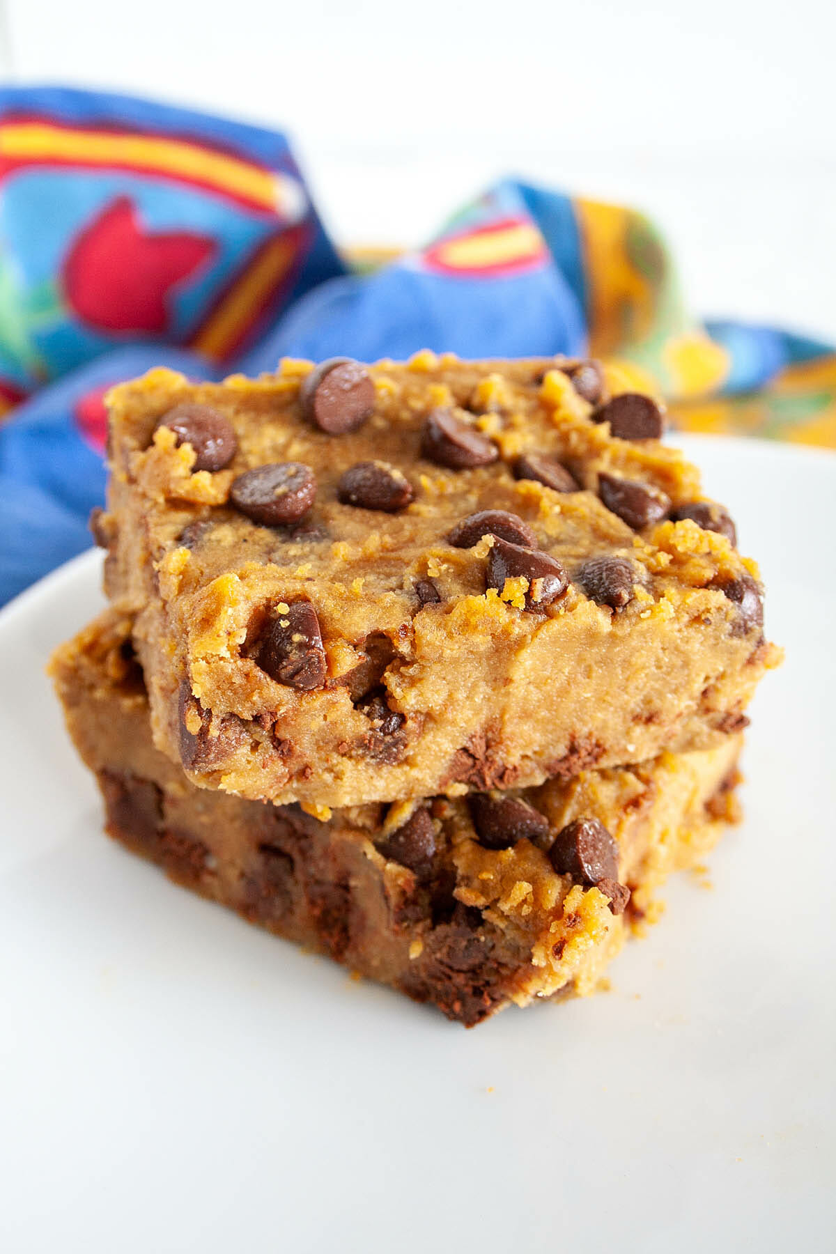 Two Pumpkin Chickpea Blondies stacked on a plate.