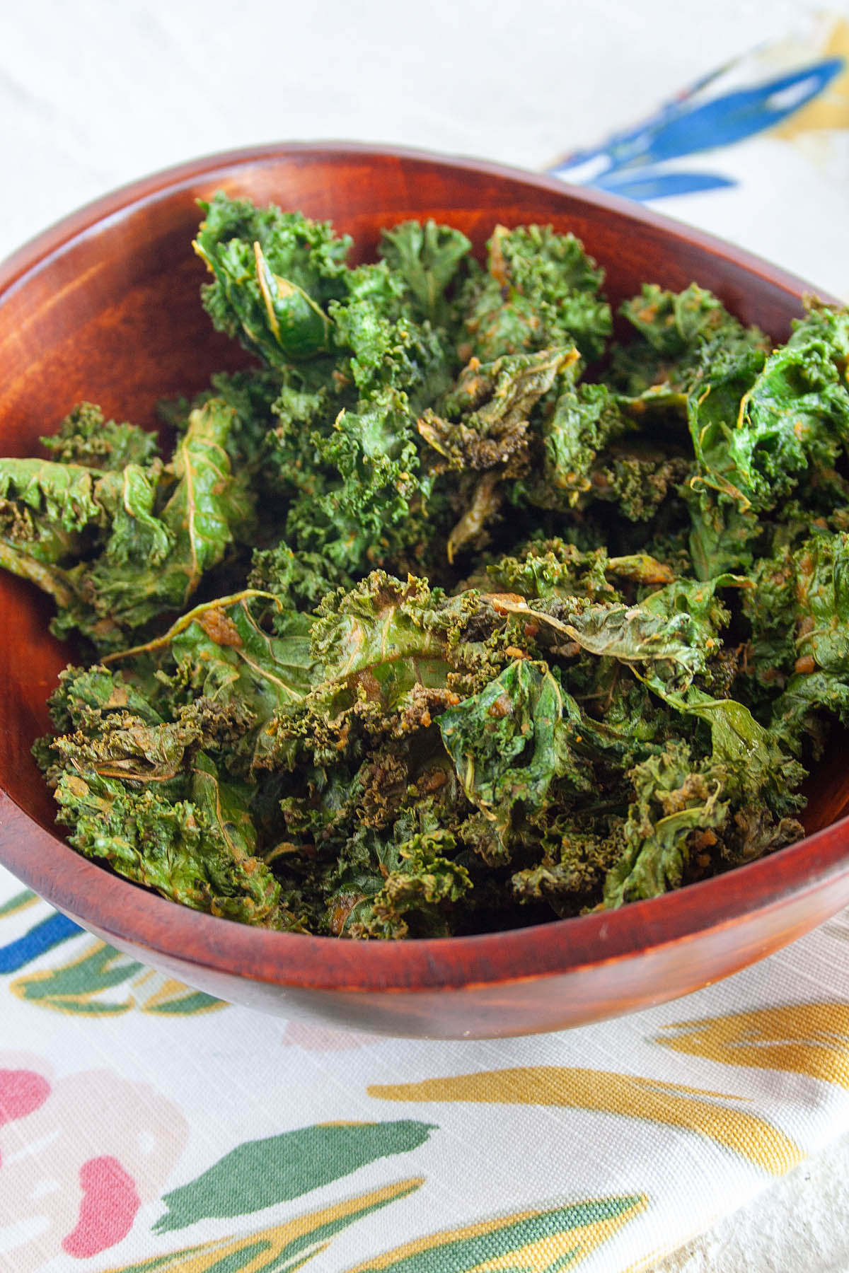 Kale Chips with Nutritional Yeast in wooden bowl.