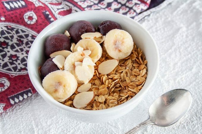 Vanilla Almond Granola in bowl with sliced banana and cherries.