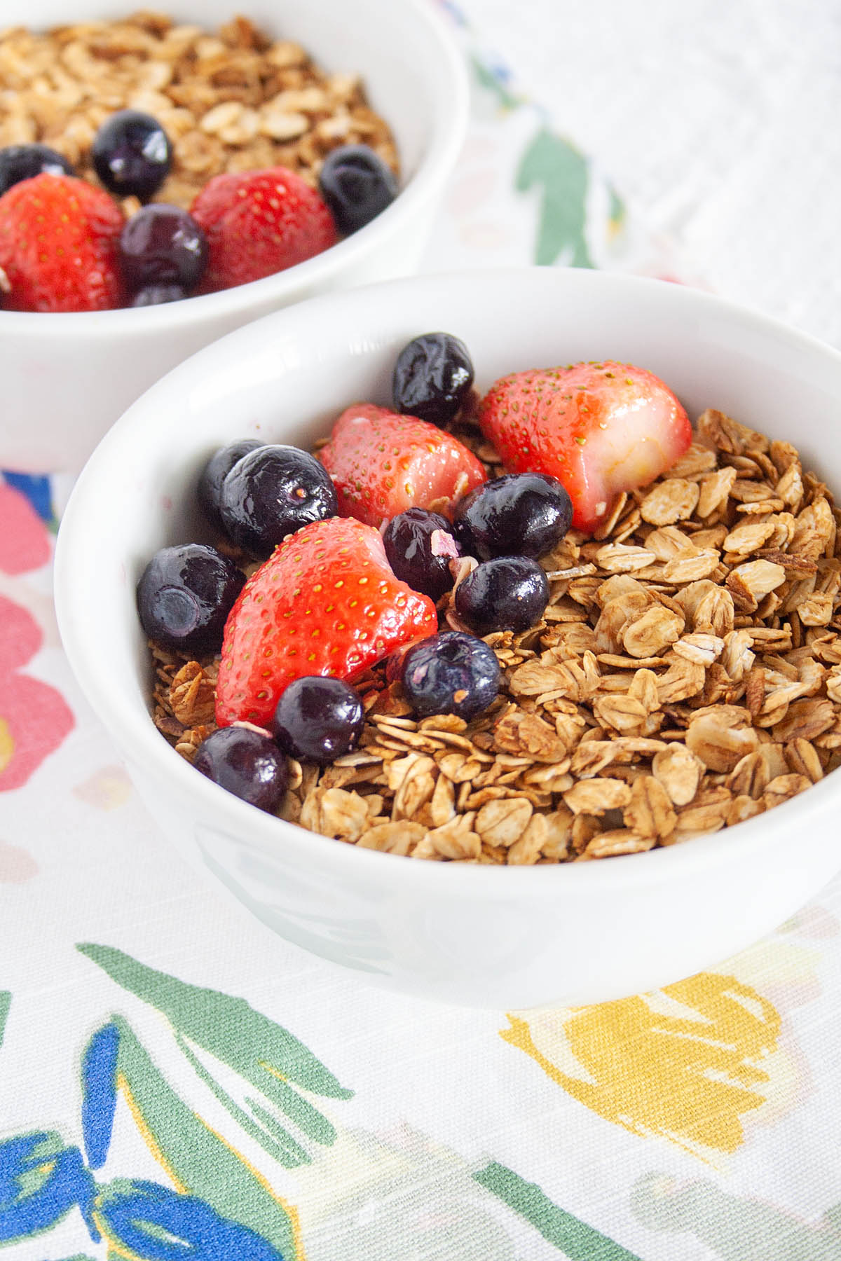 Maple and Molasses Granola in bowls with berries.