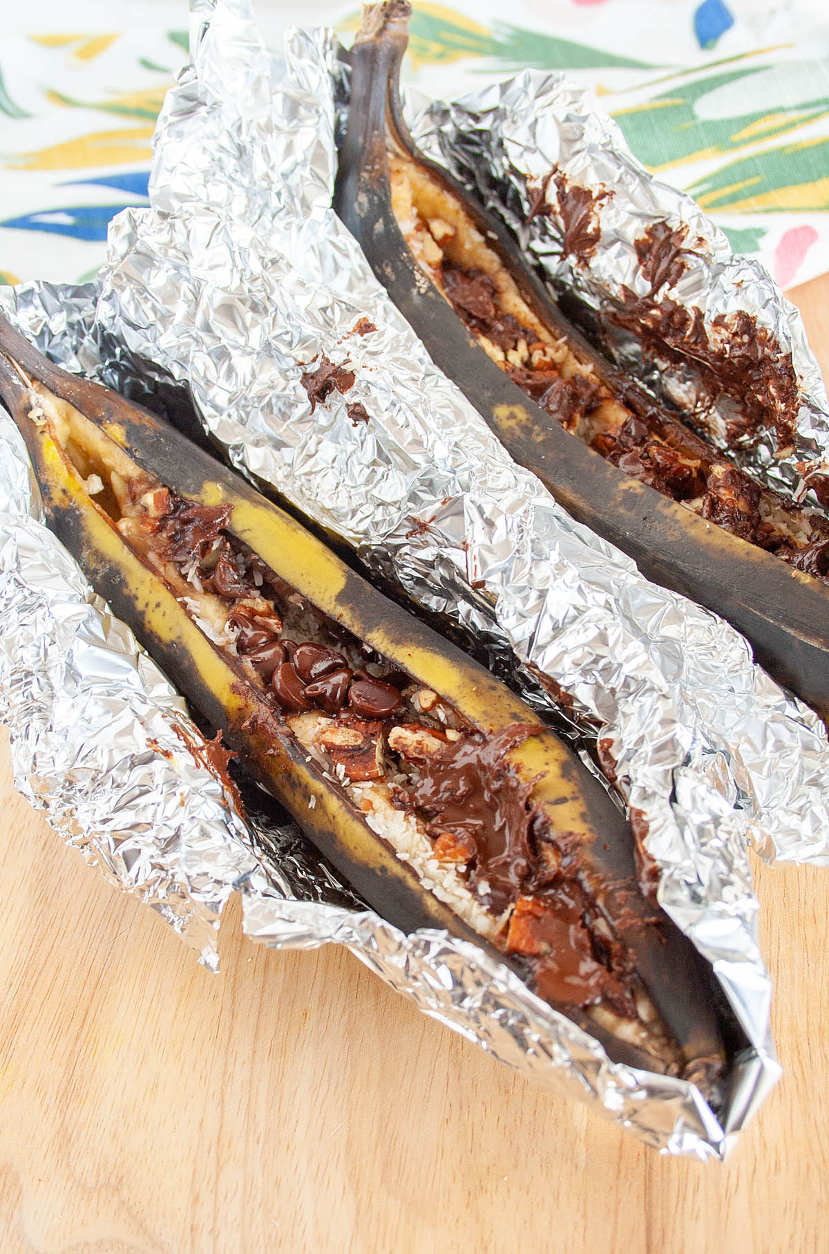 Campfire Stuffed Bananas in tinfoil on cutting board.