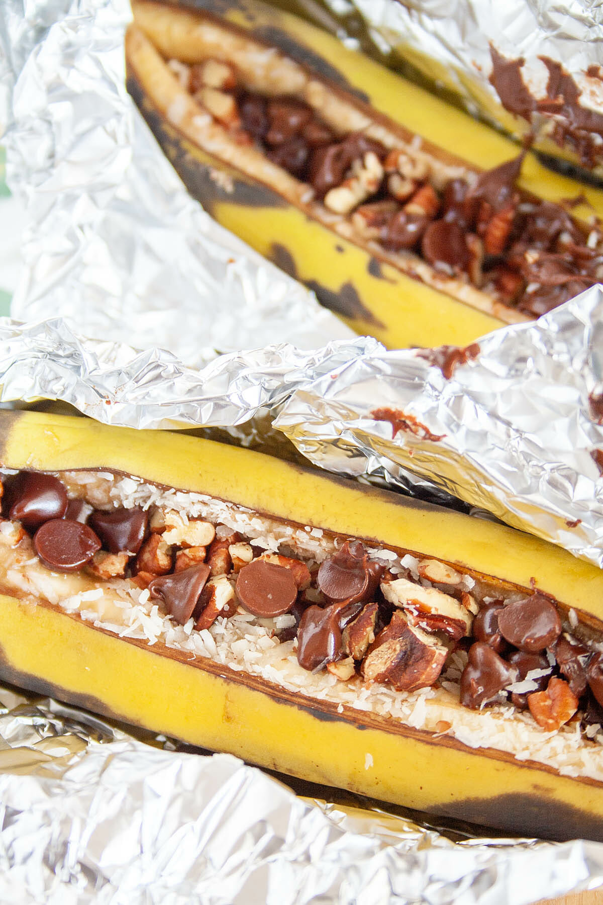 Two Campfire Stuffed Bananas in tinfoil close up.