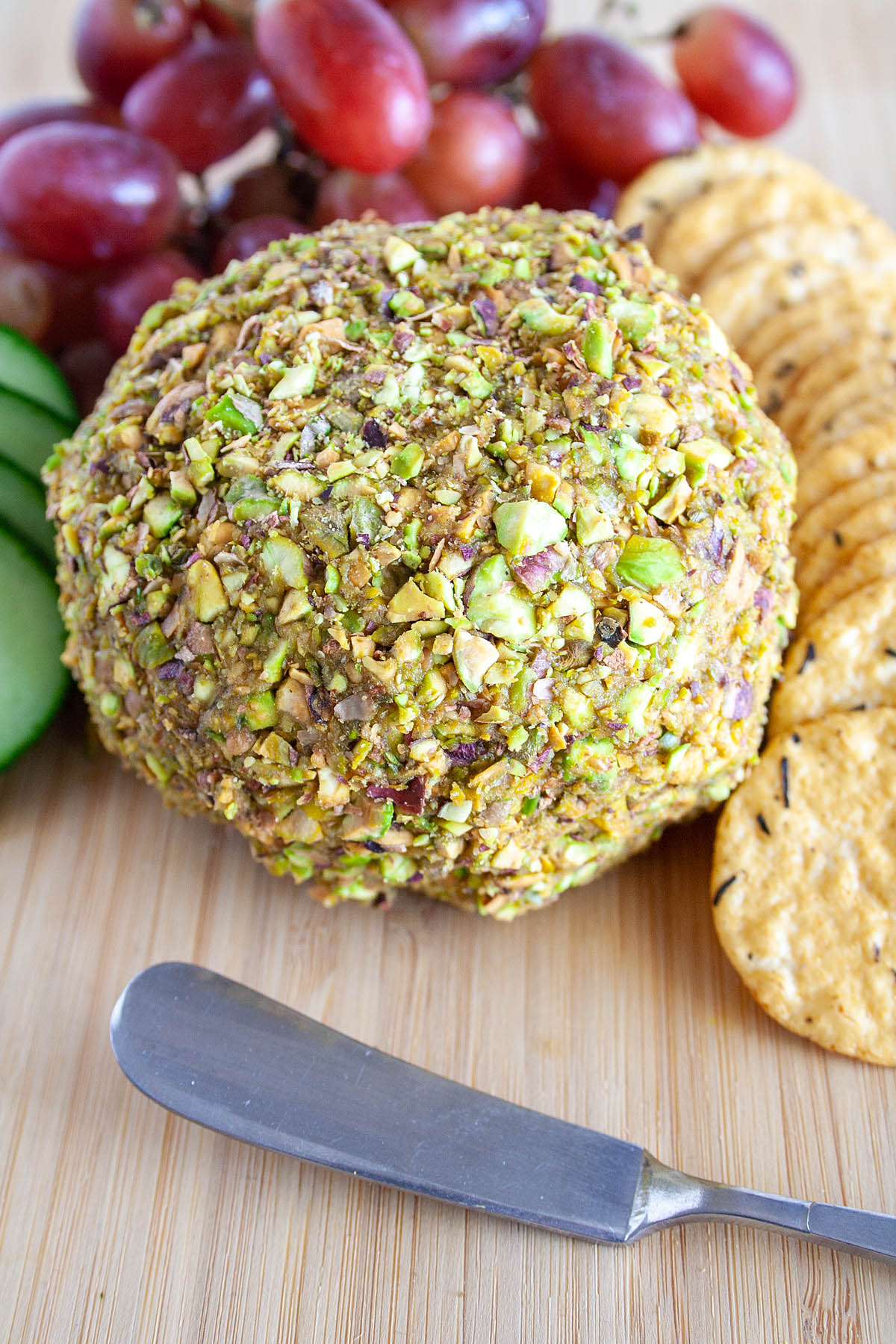 Smoky Vegan Cheese Ball on cutting board with crackers, grapes, and sliced cucumber.