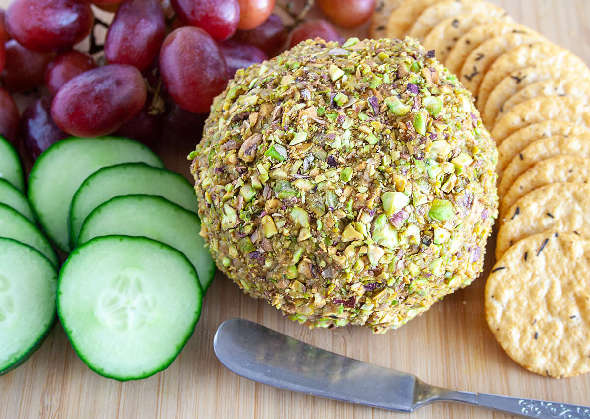 Smoky Vegan Cheese Ball on cutting board with sliced cucumber, crackers, and grapes.