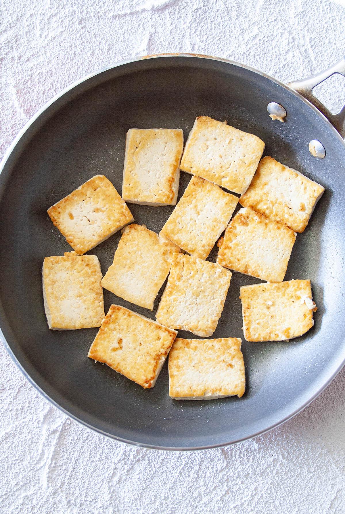 Tofu in frying pan.