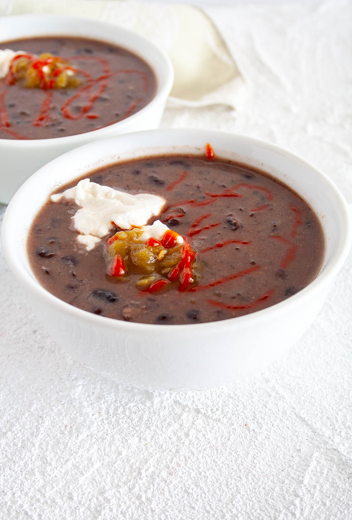 Vegan Black Bean Soup with roasted green chiles, vegan sour cream, and hot sauce on top.