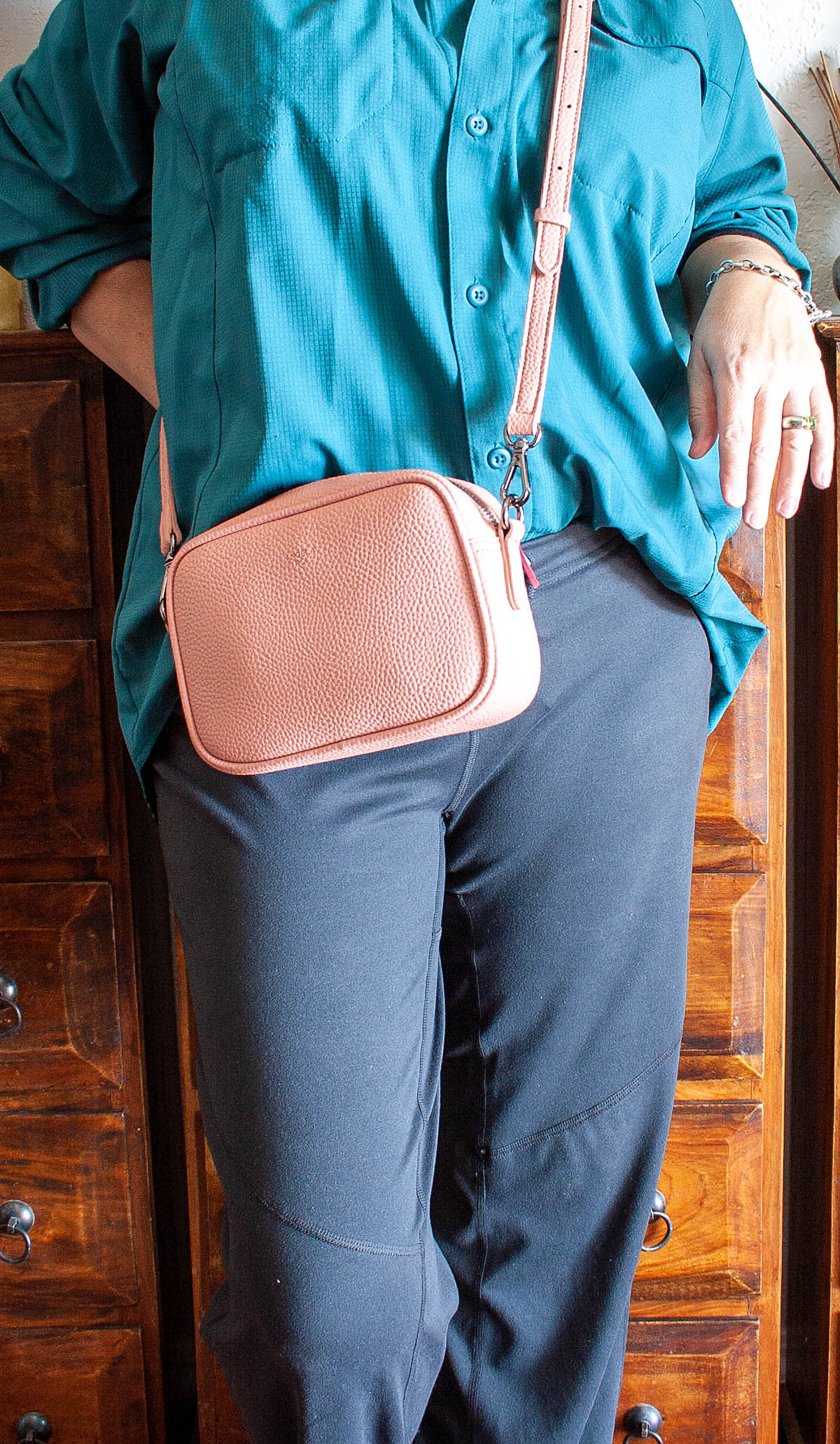 Grace Micro Crossbody in coral pink with vegan leather strap on me.
